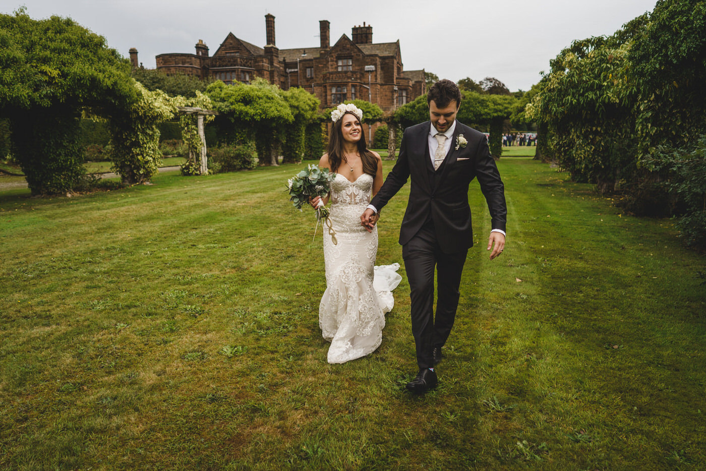the bride smiles broadly at her groom as they walk among the trees at Thornton Manor