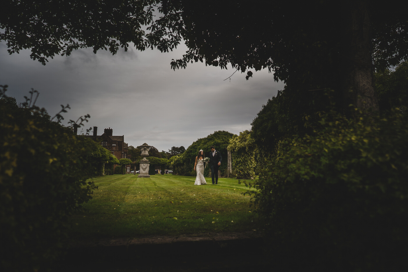 the newlyweds walk towards an opening in the gardens on their wedding day