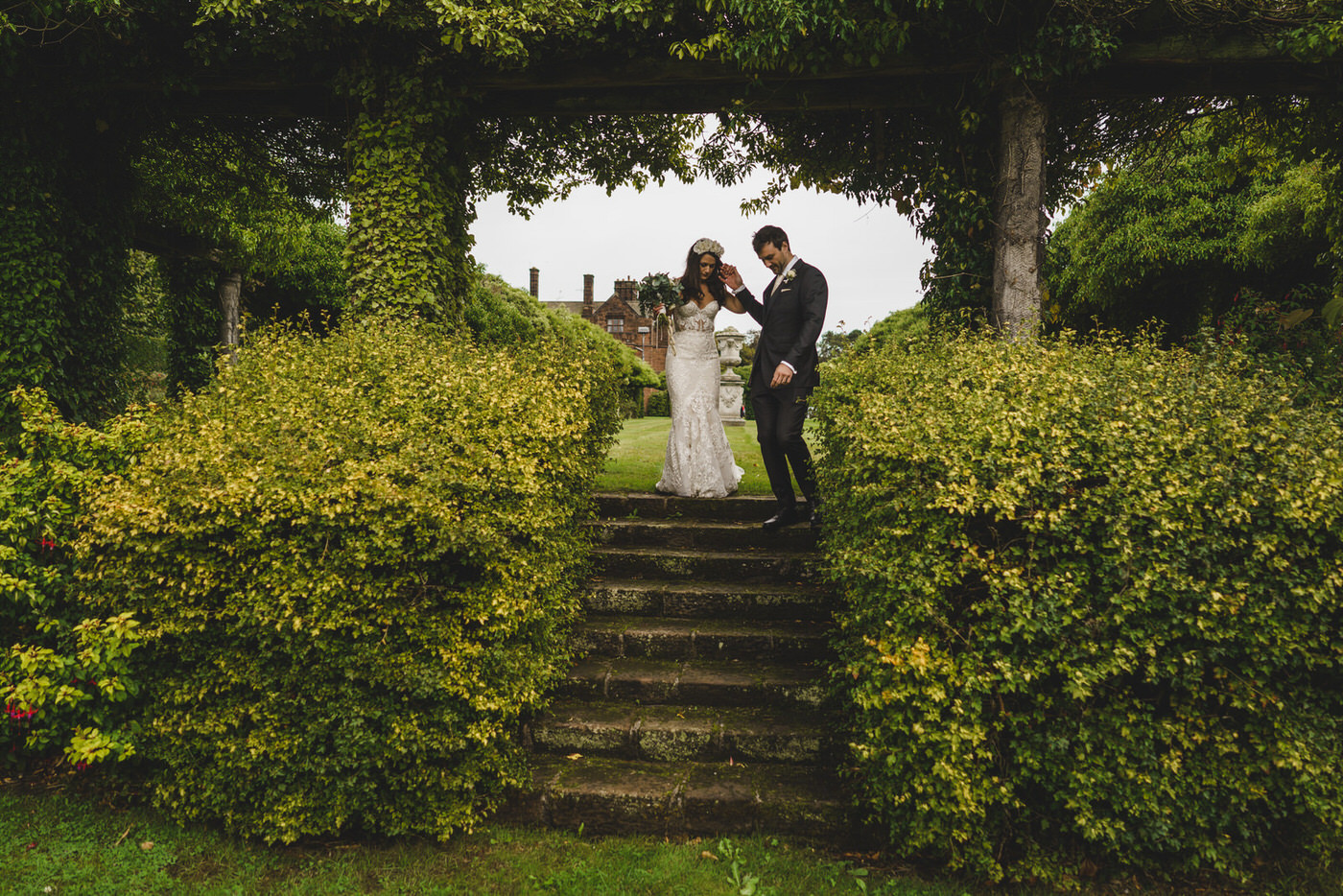 the groom helps his bride down some steps in the gardens of Thornton Manor
