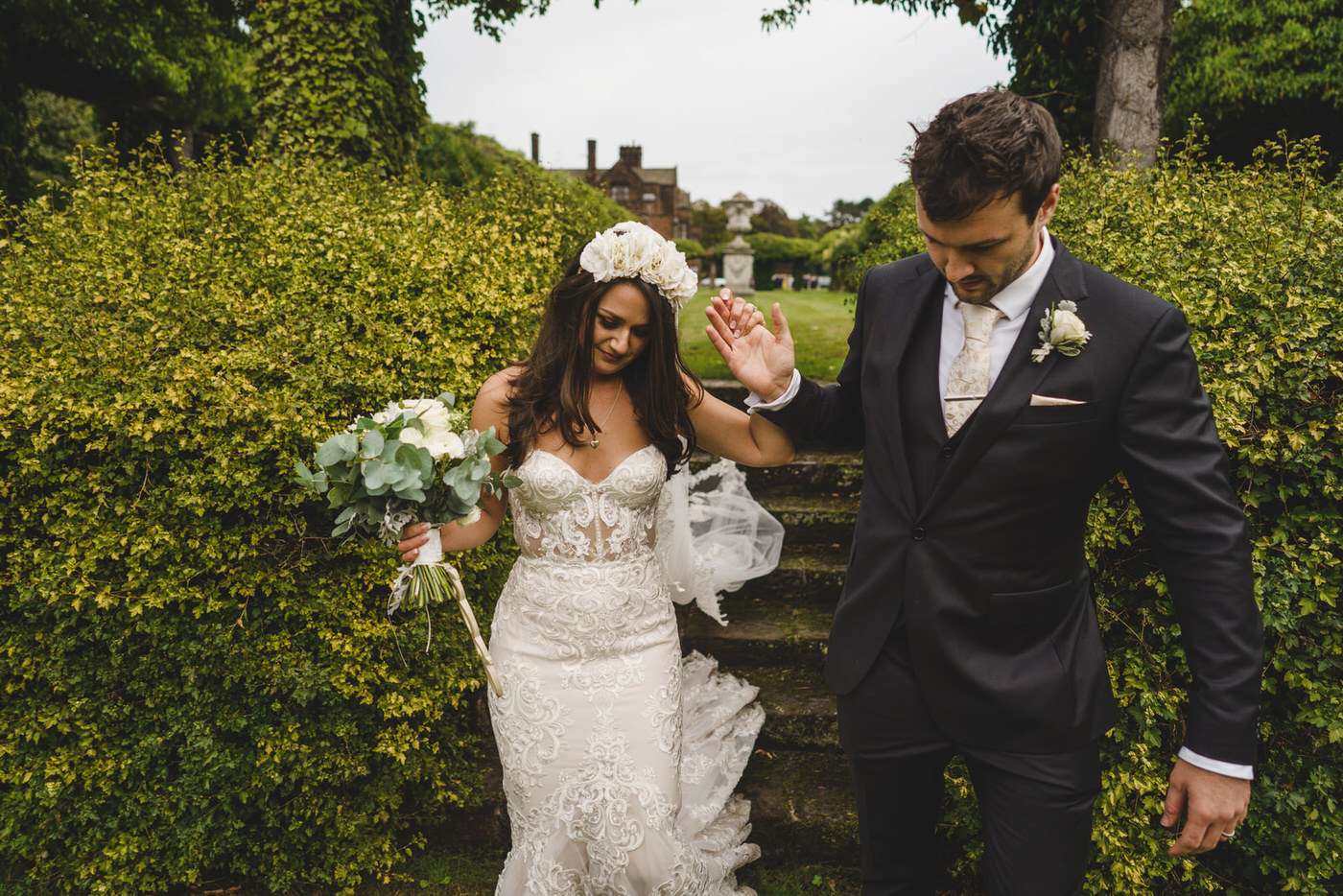 a helping hand from the groom to his beautiful bride as she holds onto her wedding bouquet