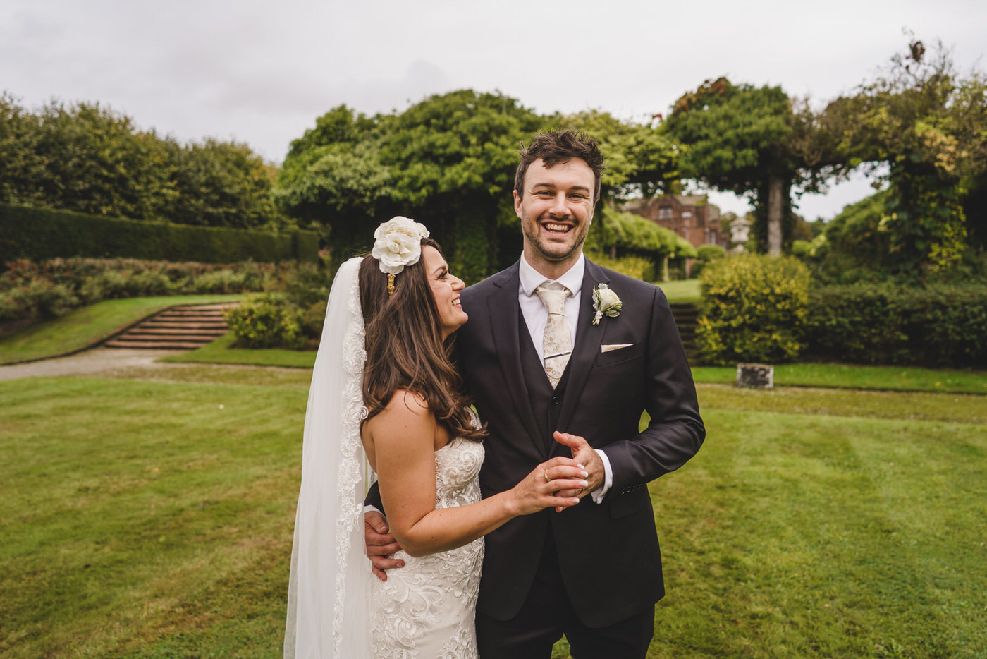 the groom laughs and smile broadly as his beautiful bride looks proudly on