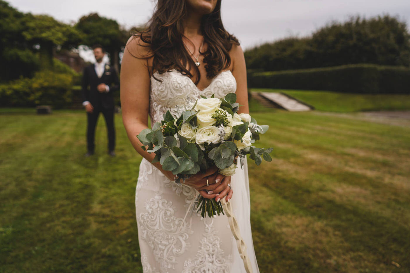 the bride holding her beautiful bouquet as the groom looks on