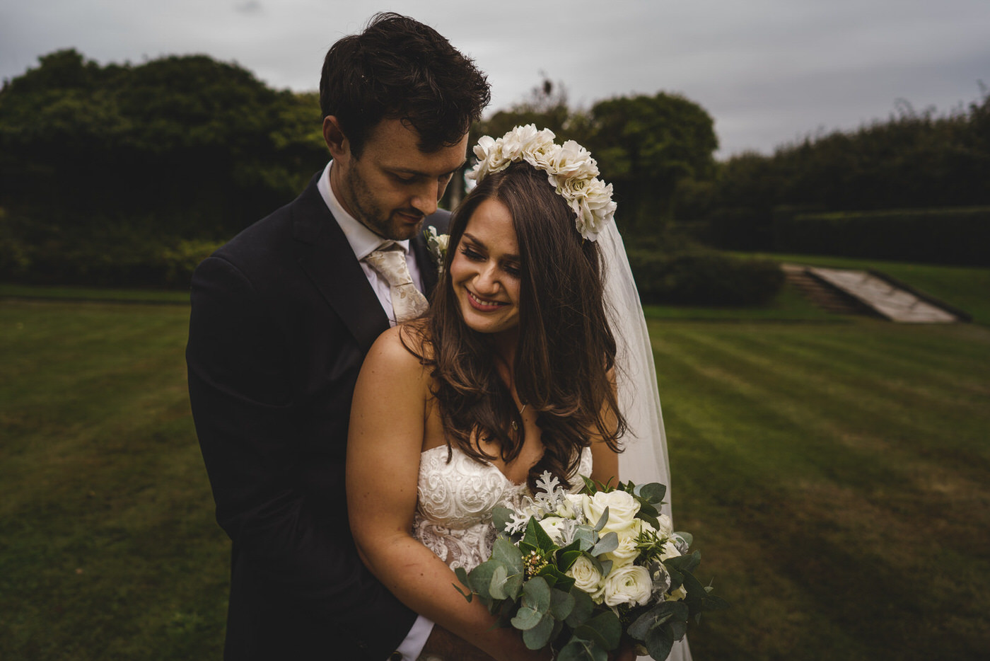 the bride and her groom have a hug while the bride holds onto her wedding flowers
