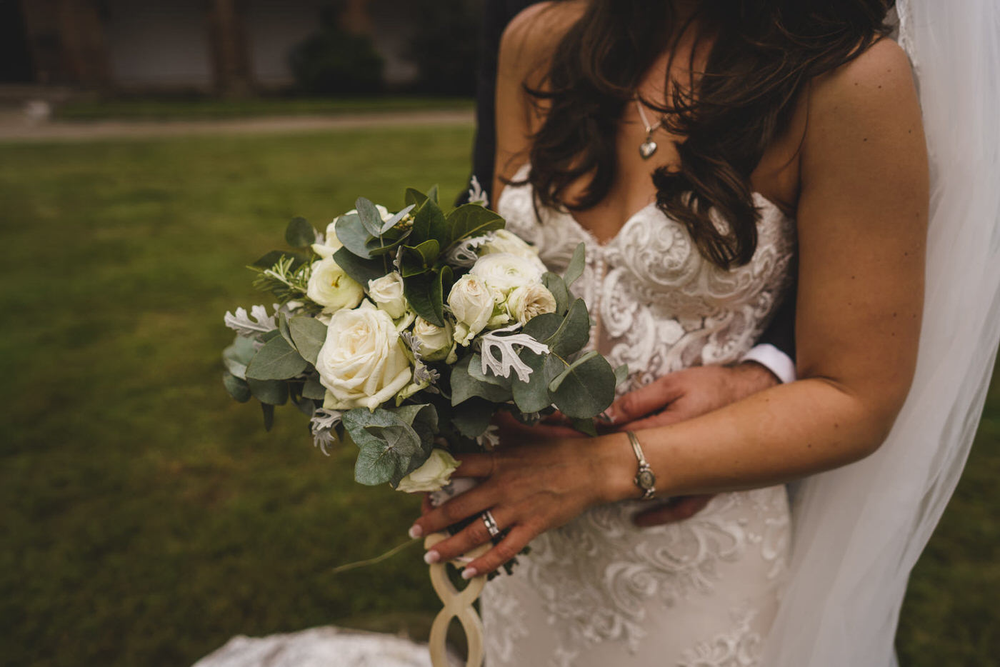 the bride's jewelry and her wonderful wedding bouquet take centre stage as the groom holds her tightly