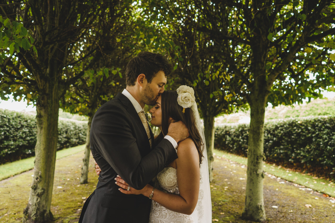 the groom tenderly kisses his bride on the forehead