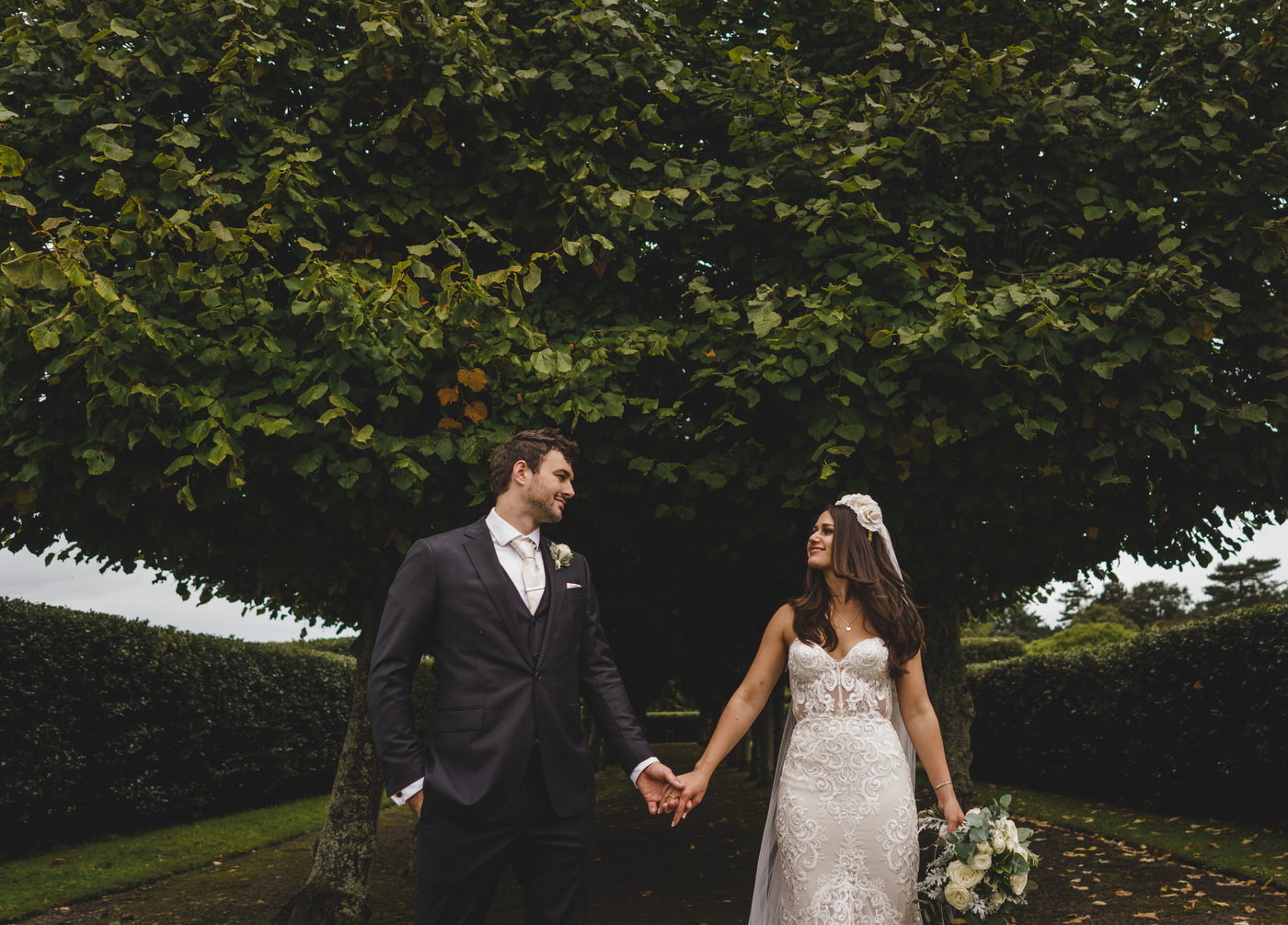 the bride and groom look at each other in front on a row of trees in the gardens of Thornton Manor