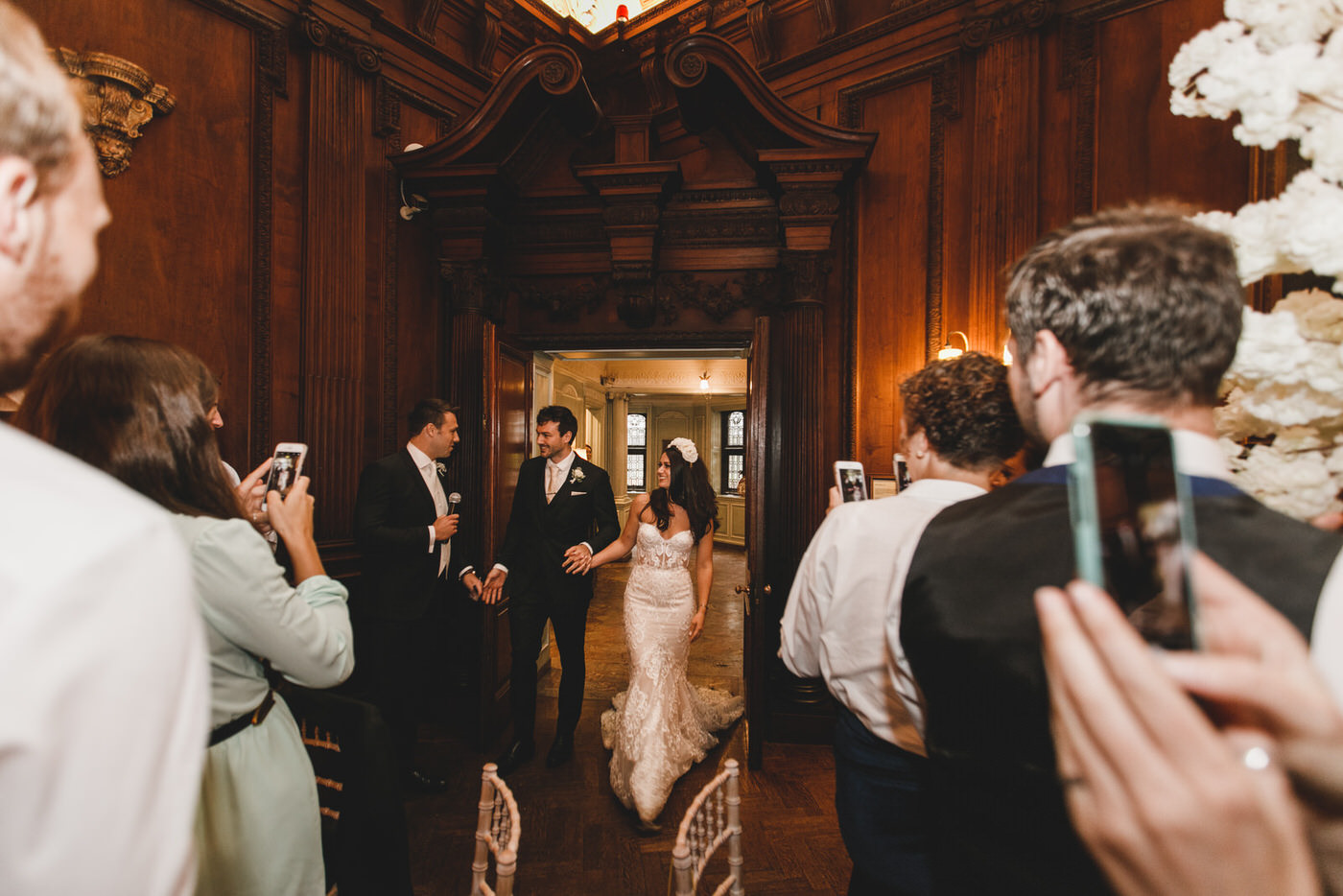 the bride and groom make their entrance into the wedding reception