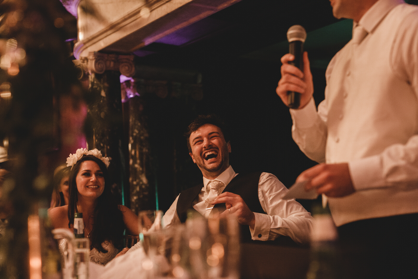 the groom laughs loudly as the guests listen to the best man's speech