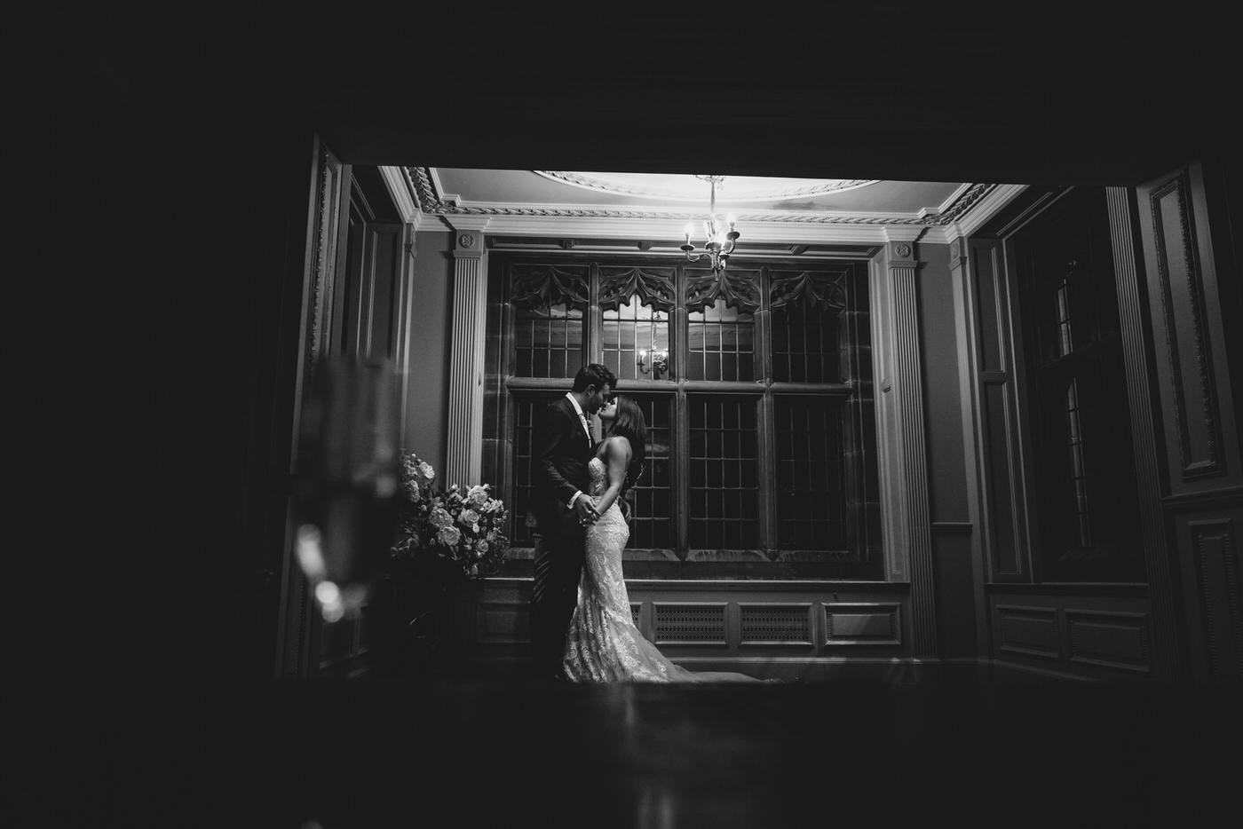 a beautiful monochromatic image of the bride and groom by a window