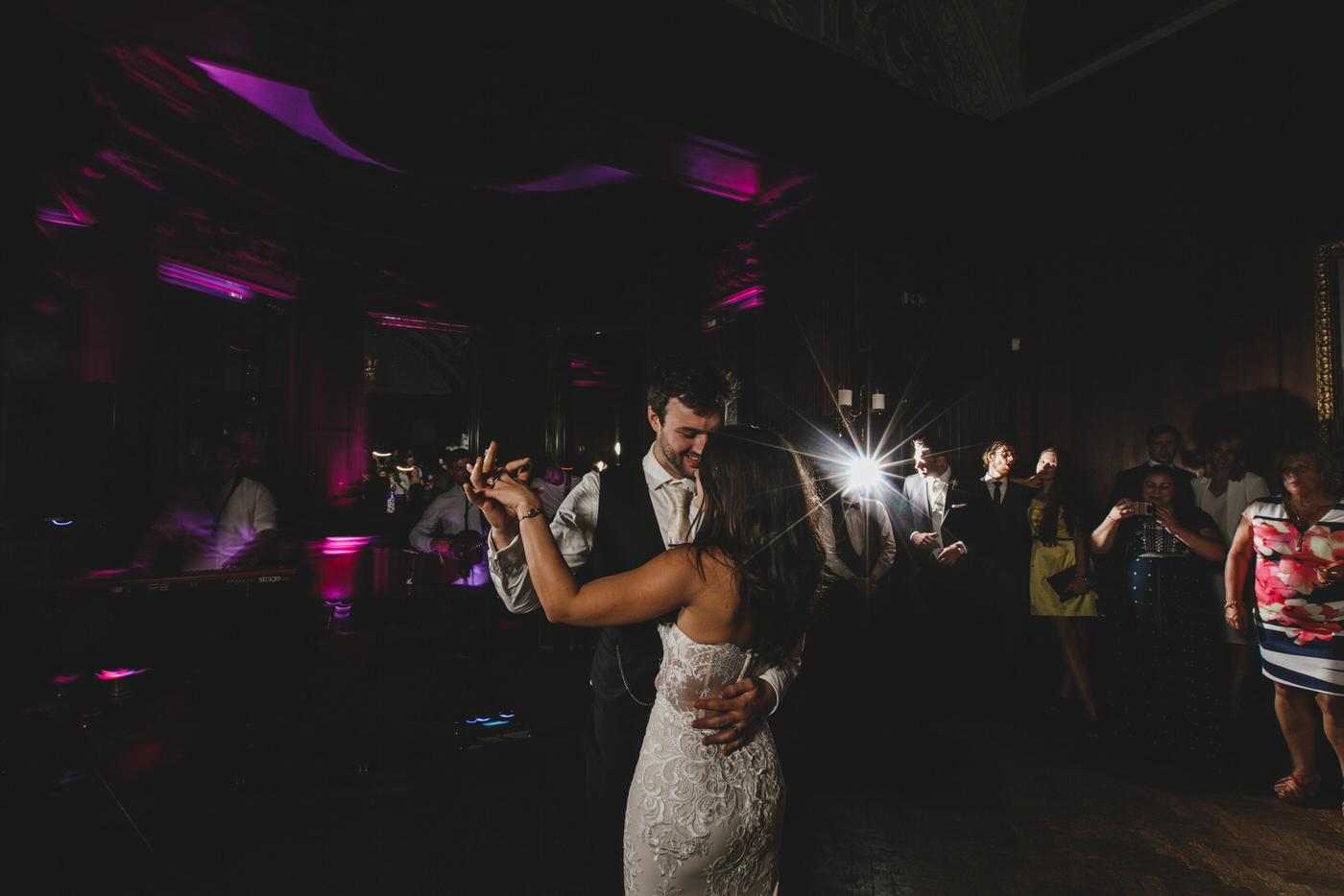 guests look on as the bride and groom enjoy their first dance