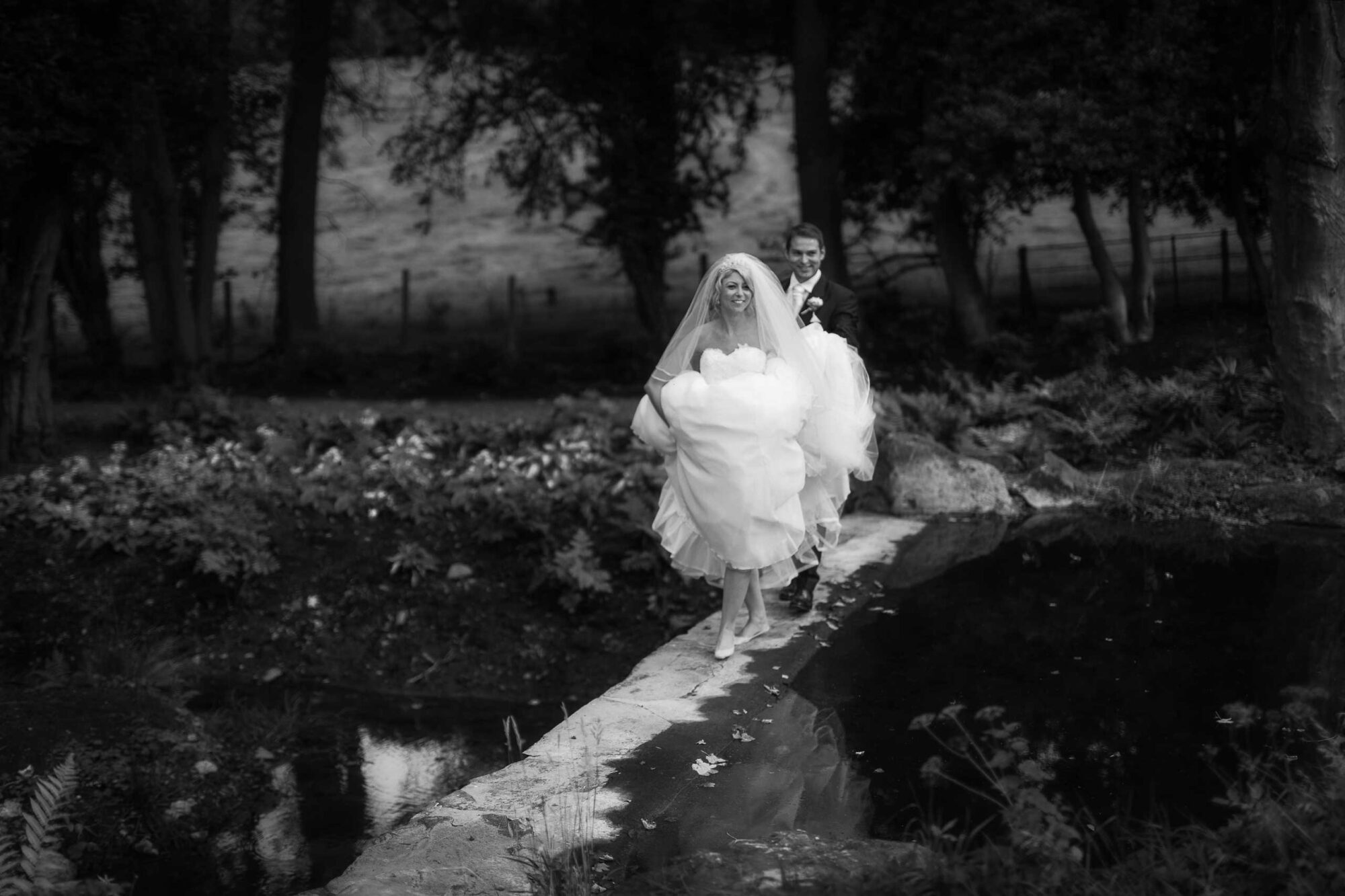 Bride and groom take a walk across a waterfall at Tyn Dwr Hall