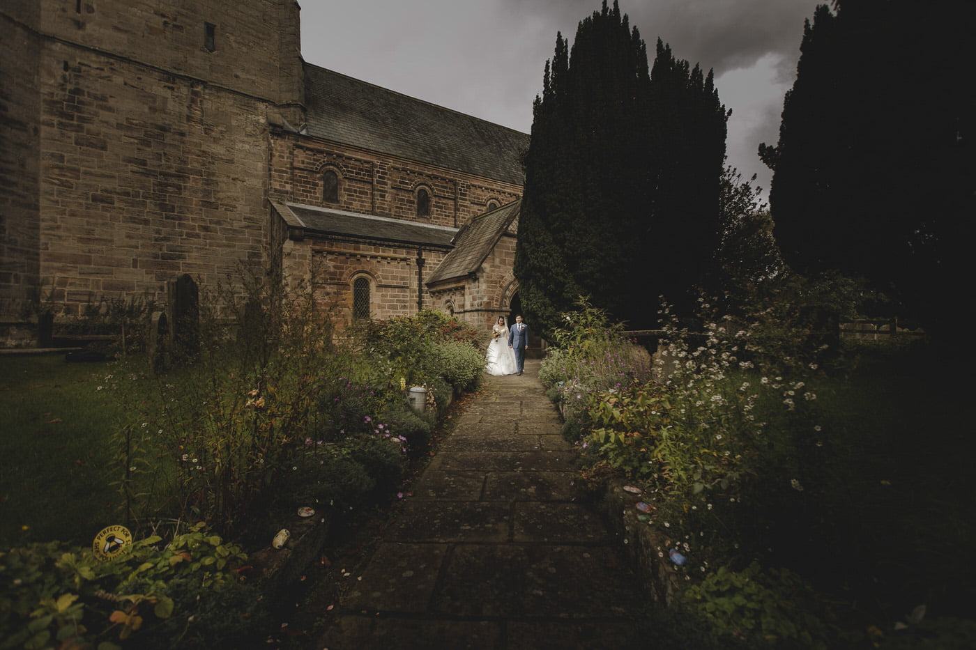the bride and groom leave the church in Yorkshire with their wedding photographer