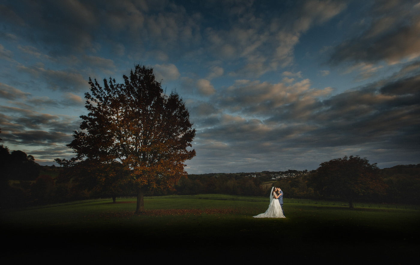 The bride and groom under an amazing sunset sky