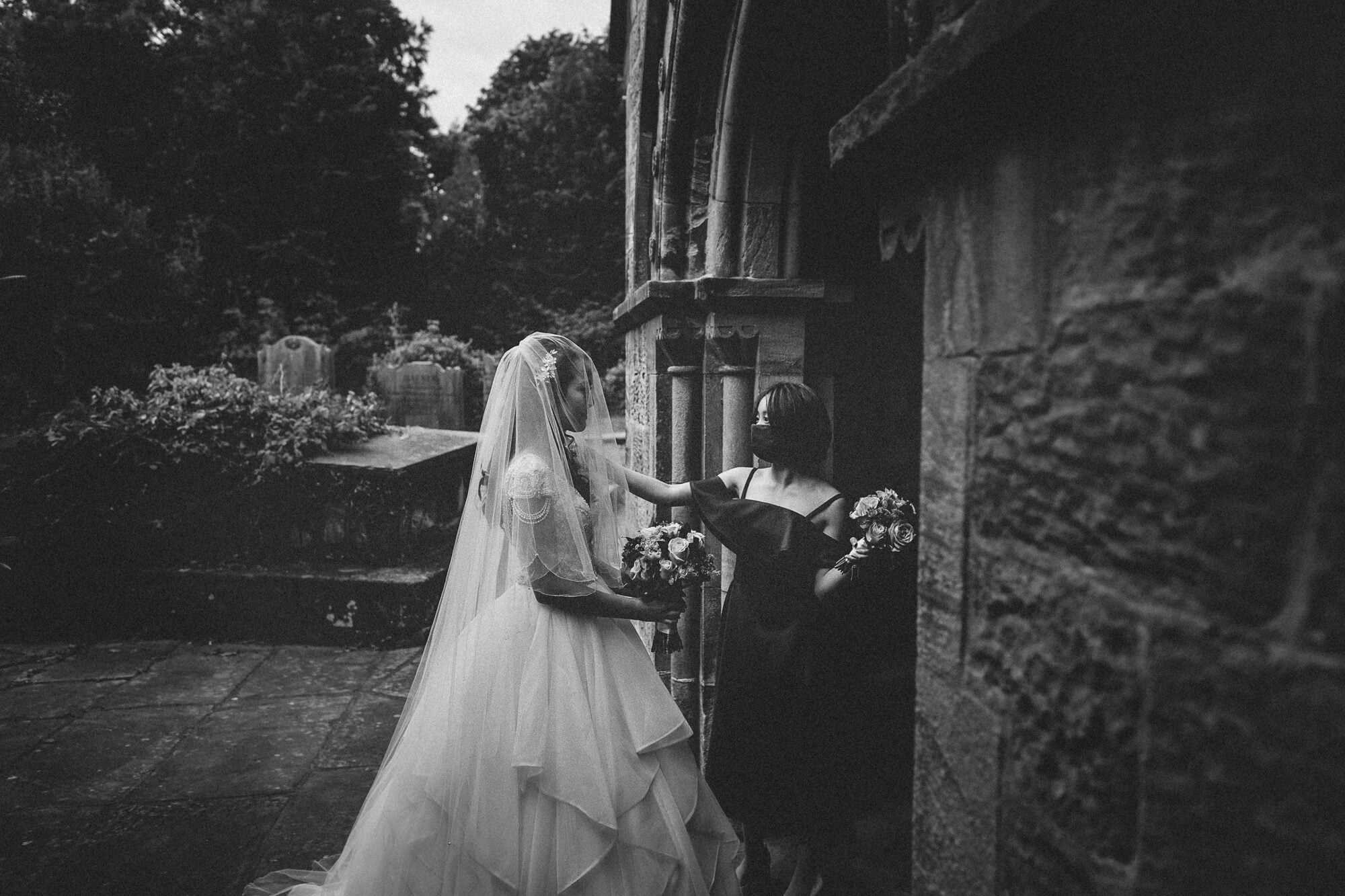 A beautiful shropshire bride awaits outside the church with her bridesmaid