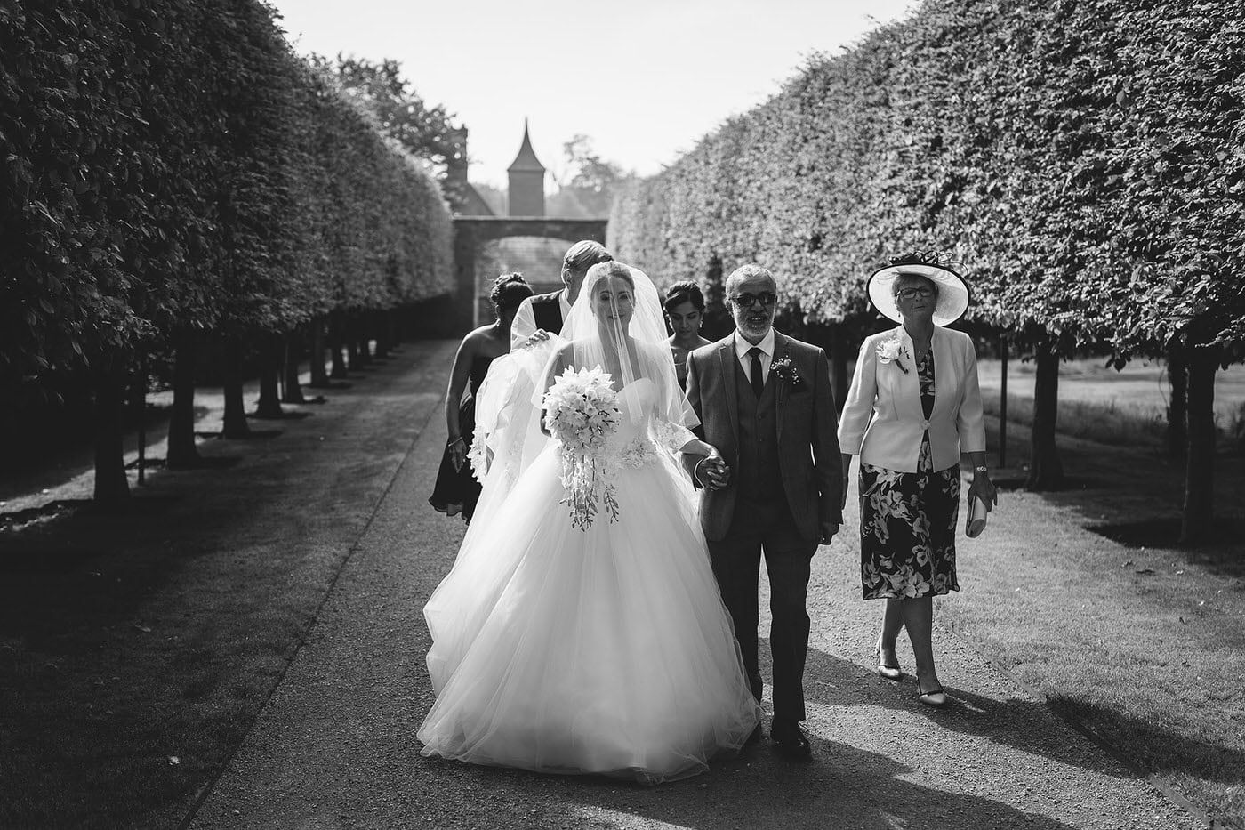 Bridal party making their way to the ceremony at combermere abbey wedding venue