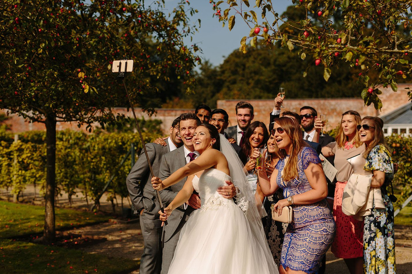 Bride and groom with guess take a selfie at combermere abbey wedding venue
