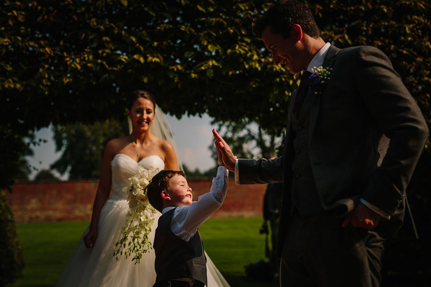 Bride and groom with young guest at combermere abbey wedding venue