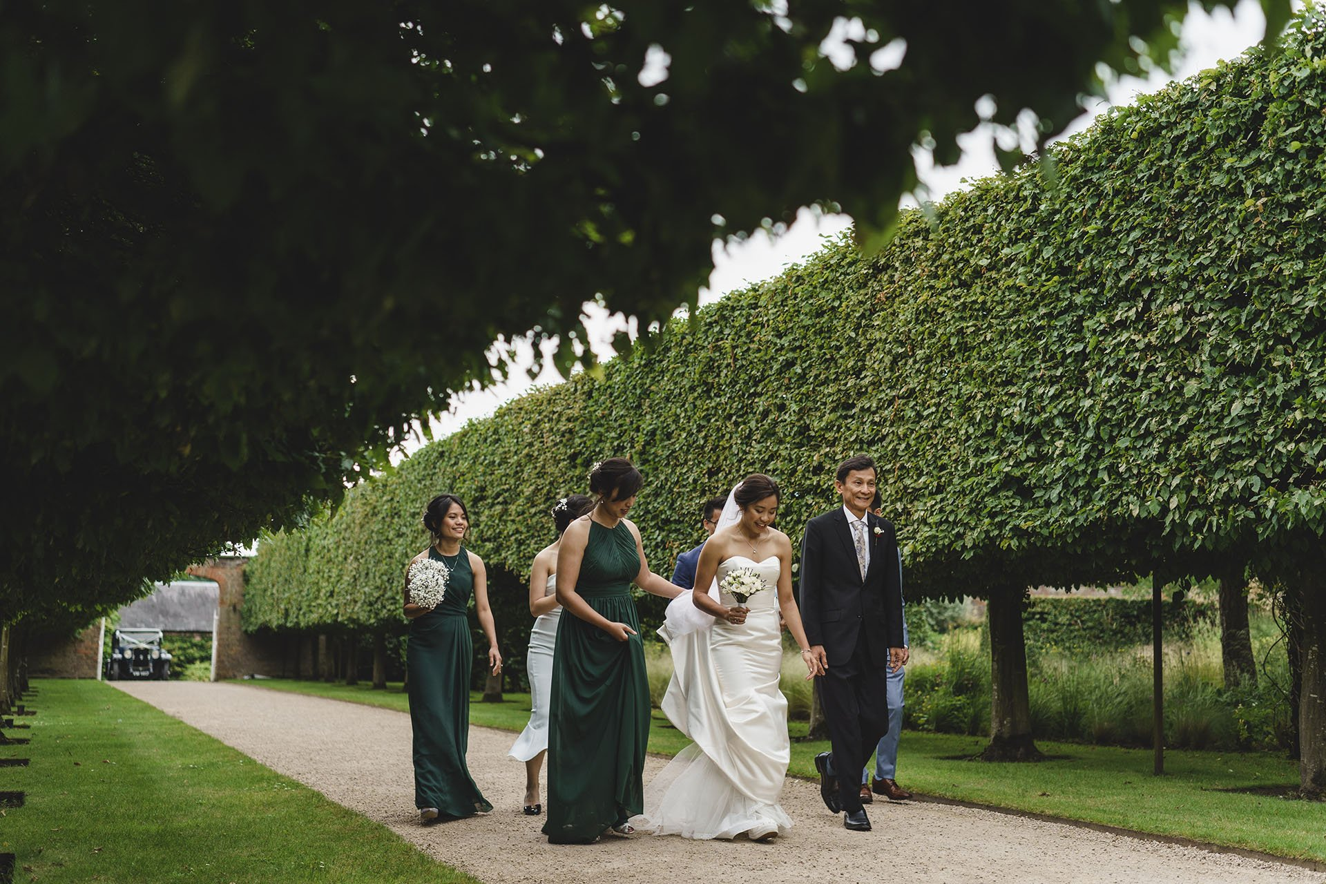 the bridal party make their way to the wedding ceremony at combermere abbey on the shropshire and cheshire border